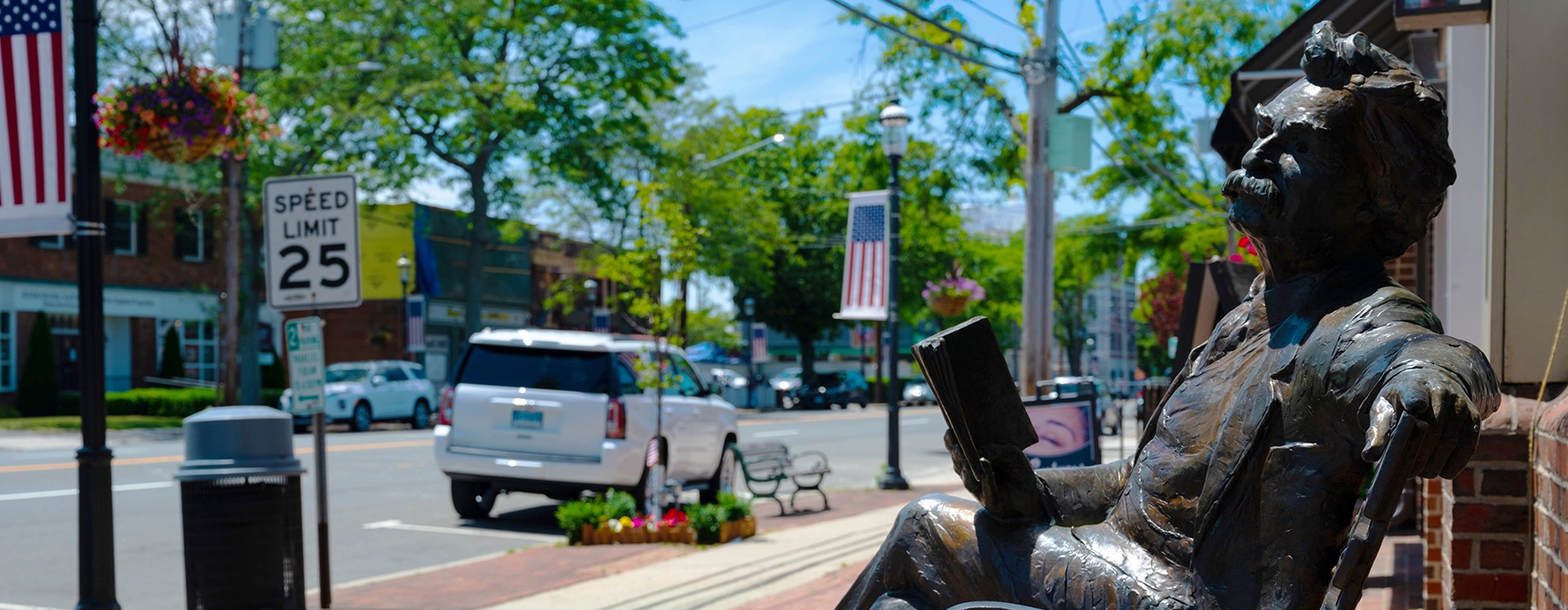 sunny day street and sidewalk image with bronze statue of man sitting on a bendch